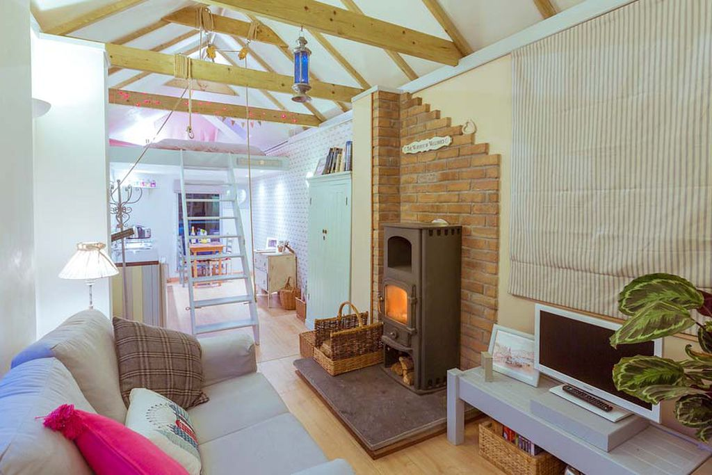 The Old Goathouse Cornwall showing the open plan lounge and kitchen with a ladder leading up to the bedroom