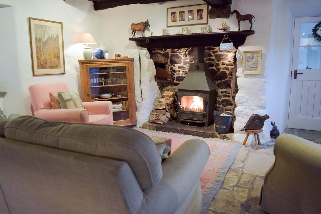 Cosy sitting room with log burner at Stares Nest Cottage in Devon