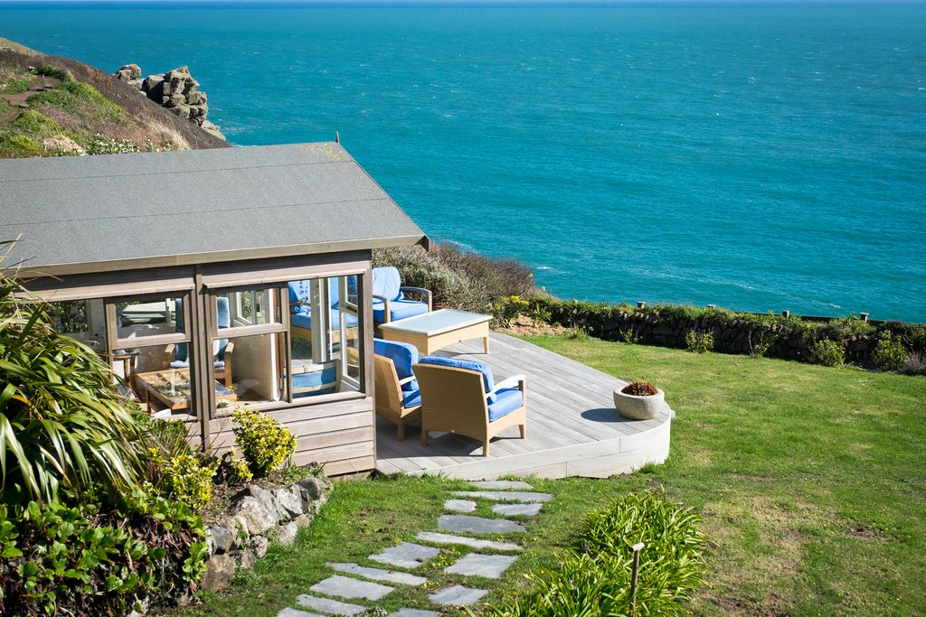 Bay House with comfy chairs on the terrace overlooking the garden and the sea