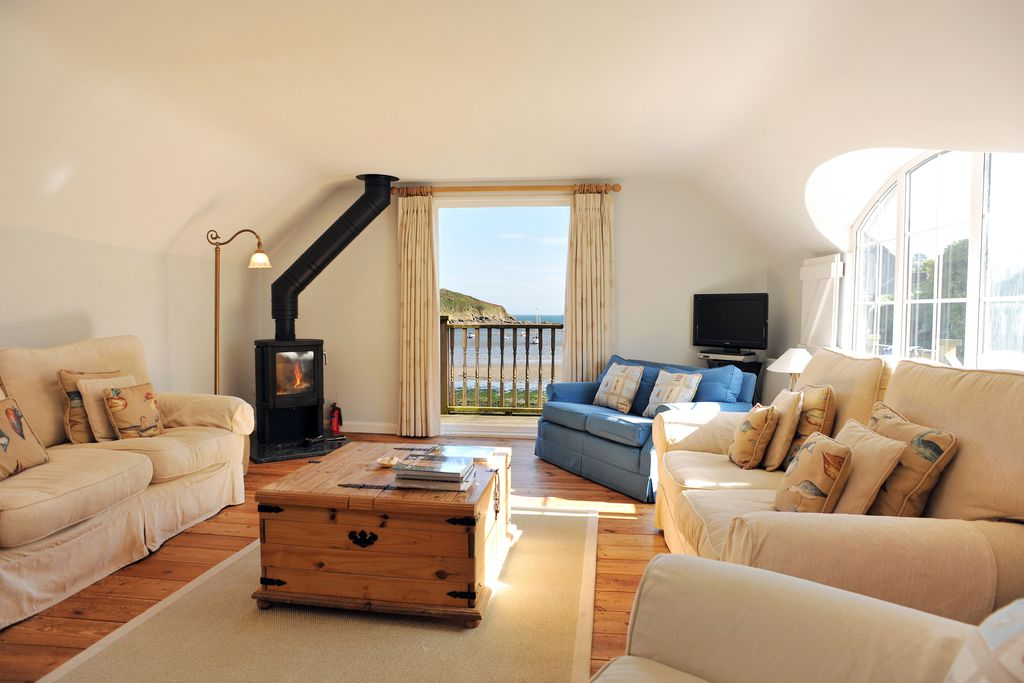 Cosy lounge with wood burner at The Boathouse in Manaccan, Cornwall with a balcony offering views out to sea