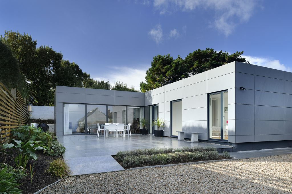 Exterior view of Ispoyntel in St Ives Cornwall, a modern architectural design property with large glass windows and an outdoor patio