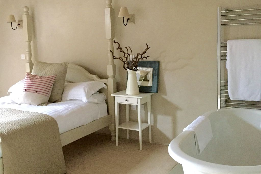 Light and airy bedroom at Winnow Nook, Derbyshire with large bath tub