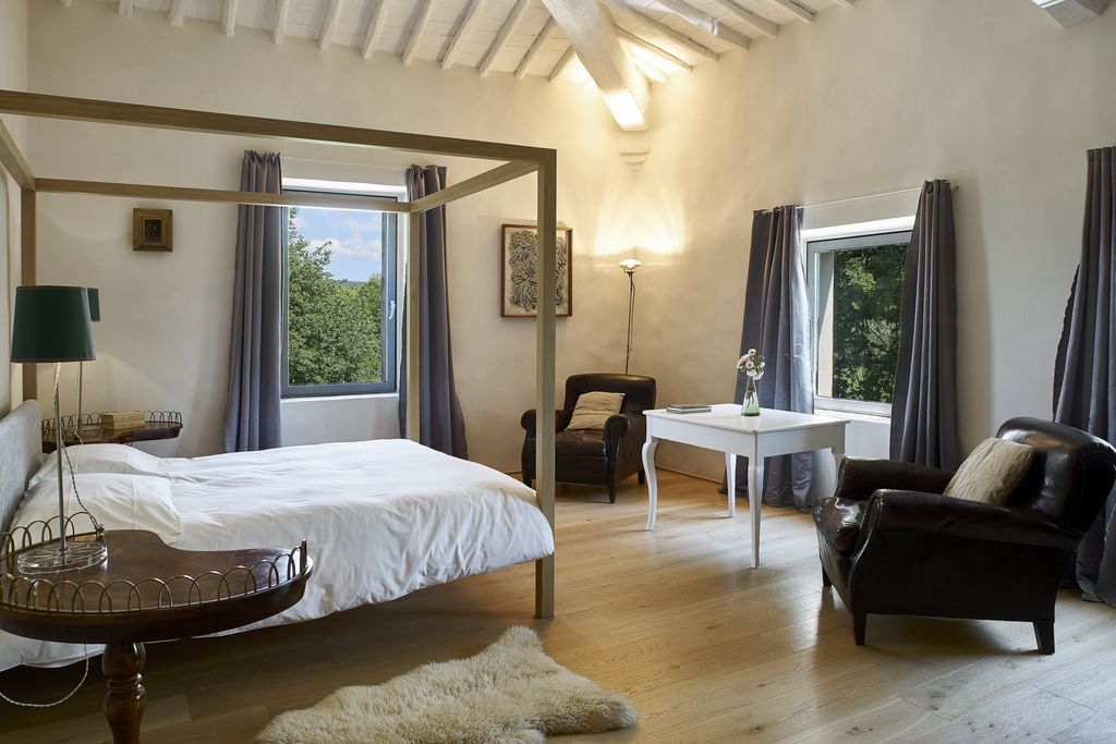 Light and airy bedroom at Casale de Cellole in Tuscany, Italy with four poster bed and two chairs and table with view of countryside