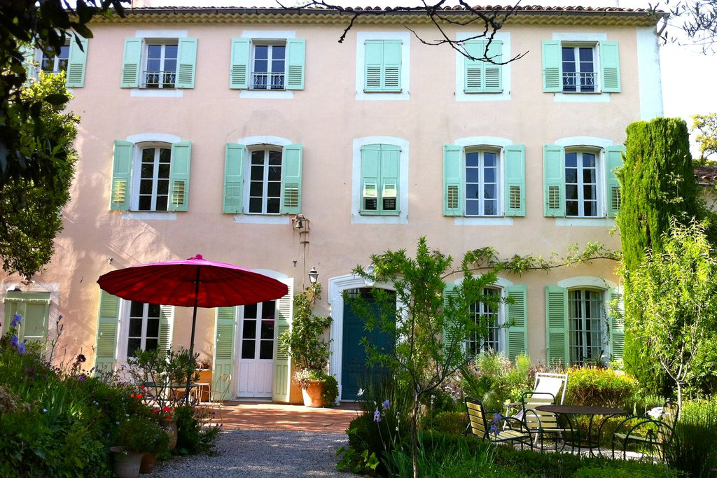 Exterior of La Bastide du Bosquet in Antibes, France with beautiful grounds and traditional wooden window shutters