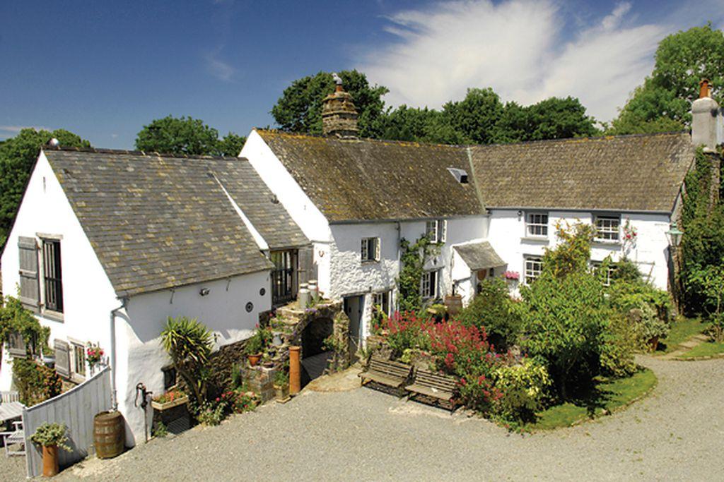 Exterior of traditional whitewashed Beara Farmhouse in Bideford, Devon