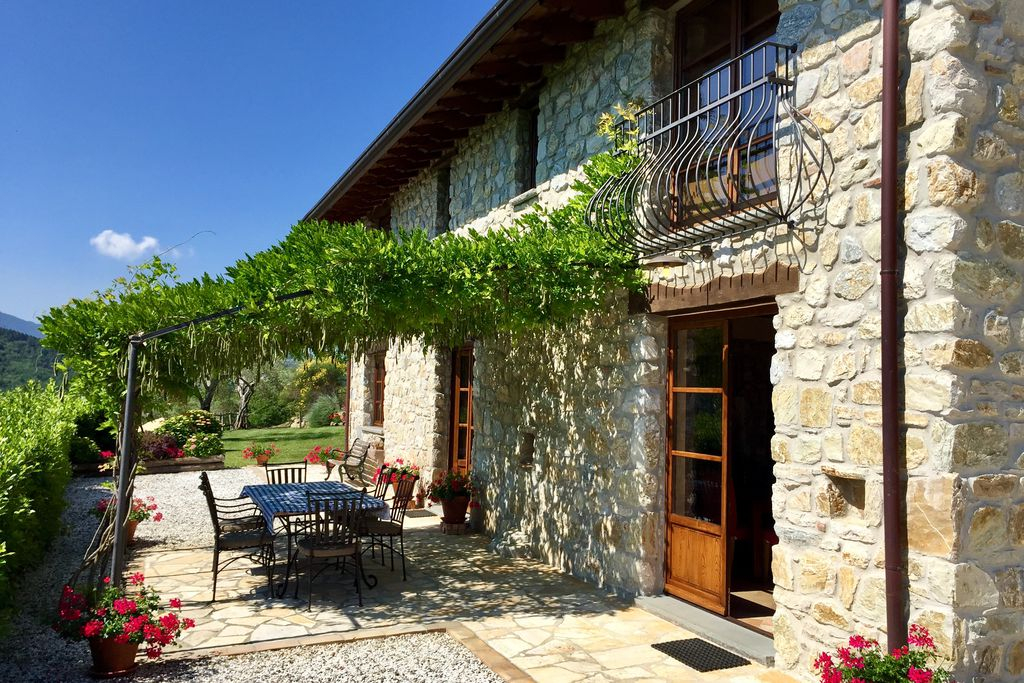 Exterior of Casa Lucia in Tuscany Italy with sunny outdoor terrace for eating al fresco and lovely garden
