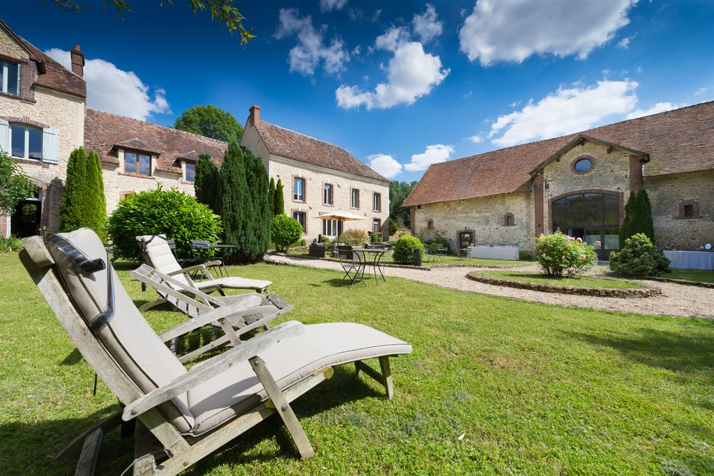 Exterior view of La Ferme de Bouchemont in the Loire Valley with pretty stone farm buildings with a courtyard garden and wooden deck chairs.