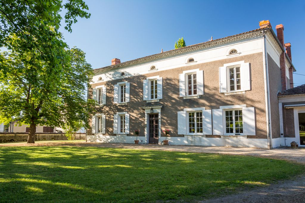 Exterior view of Préchac Park, Aquitaine which sits within the Sauternes wine region. A large tree casts dappled shade over the front of the house.