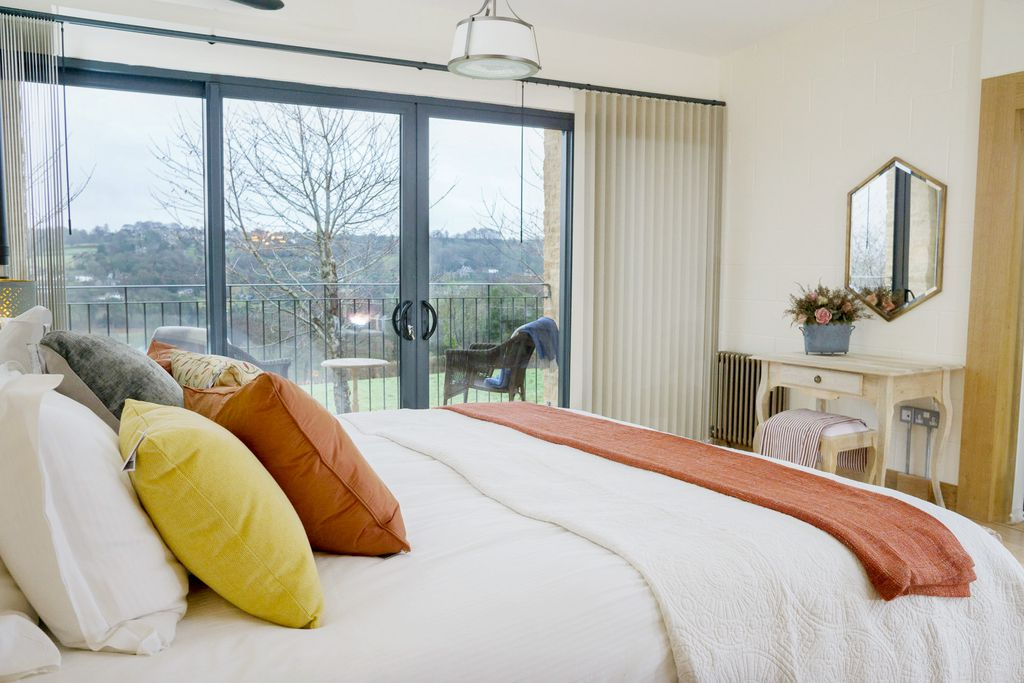Bright bedroom with colourful touches and countryside views at Woodchester Valley Vineyard Barns near Stroud