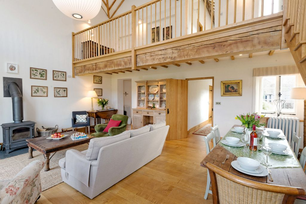 Bright and spacious living area with wood burner and view of upstairs mezzanine area at The Dairy at Collfryn Farm in Powys, Wales.