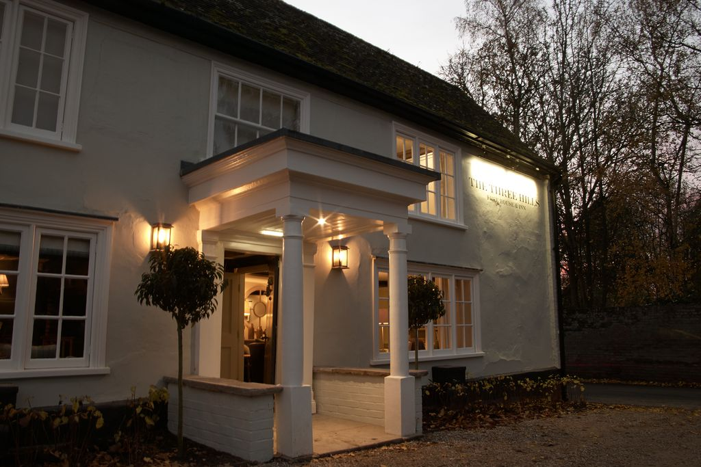 Exterior of The Three Hills pub lit up at dusk in Bartlow, Cambridgeshire