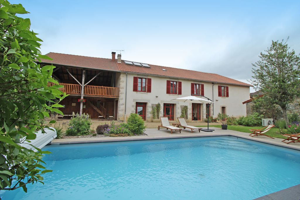 An exterior view of Les Jardins de Lily, Saint Leonard de Noblat, France; looking across the large pool you can see a lovely house with red shutters.