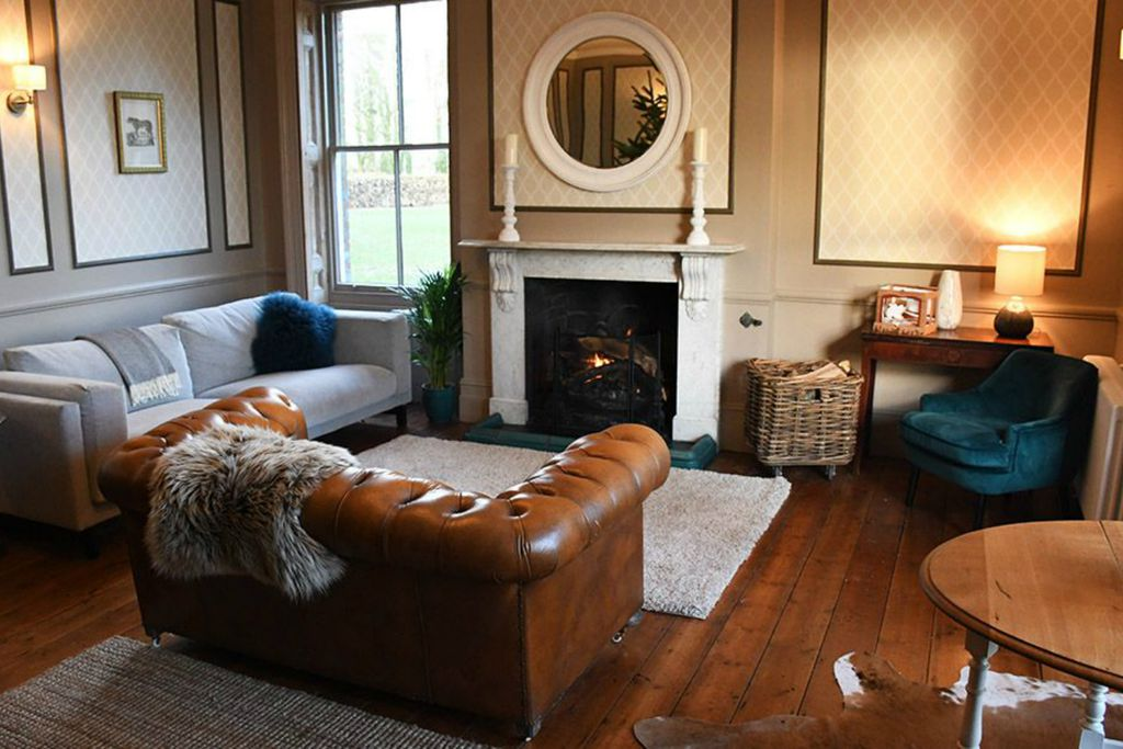 Cosy lounge with brown leather sofa and real wood burner at Abbots Court House in Winterborne Kingston, Devon