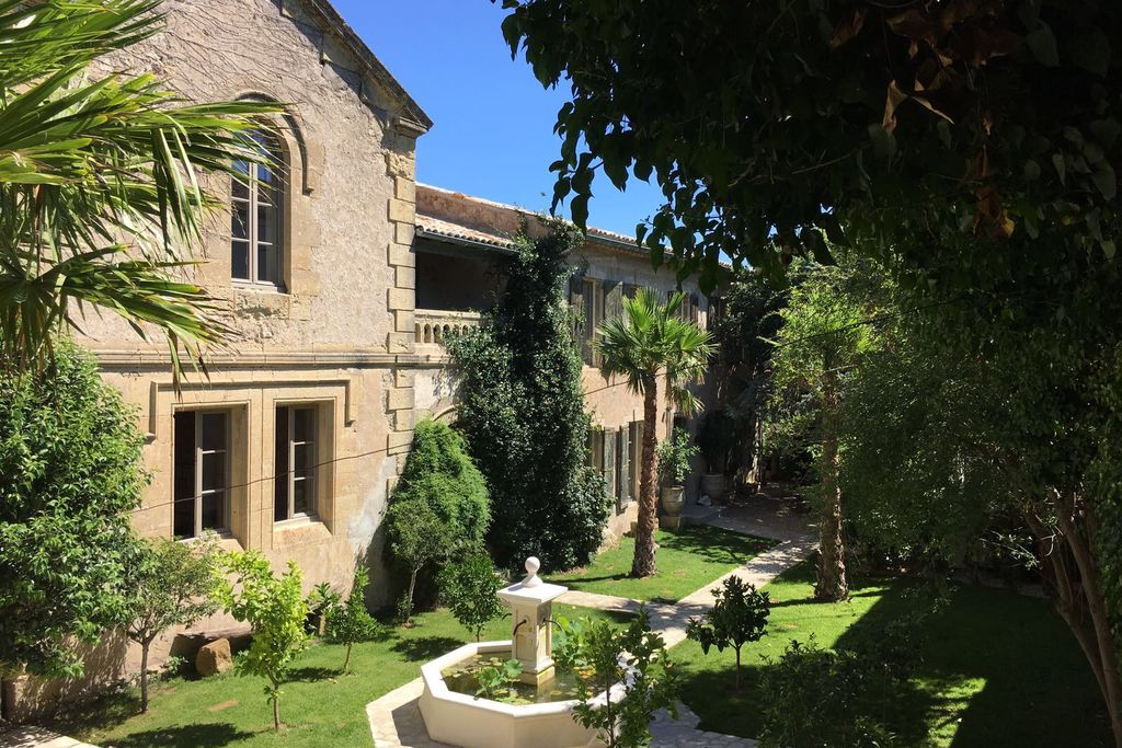 A sunny exterior photo of this beautiful old Convent in Roujan, France. There are palm trees and a water feature in the very green garden.