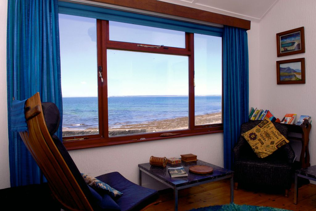 View of chairs in living room with view of sea just outside window, at Carmel in Gwynedd, Wales