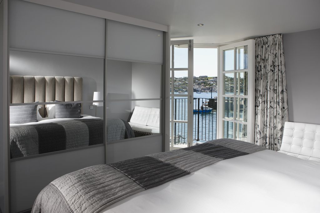Double bedroom with balcony and view out to the harbour on a sunny day