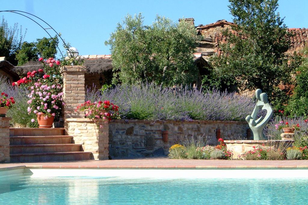 Exterior view of Podere Borgacciano, Arezzo, Italy. Pool and garden view, Lavender and flowers , bricked wall and a fountain.