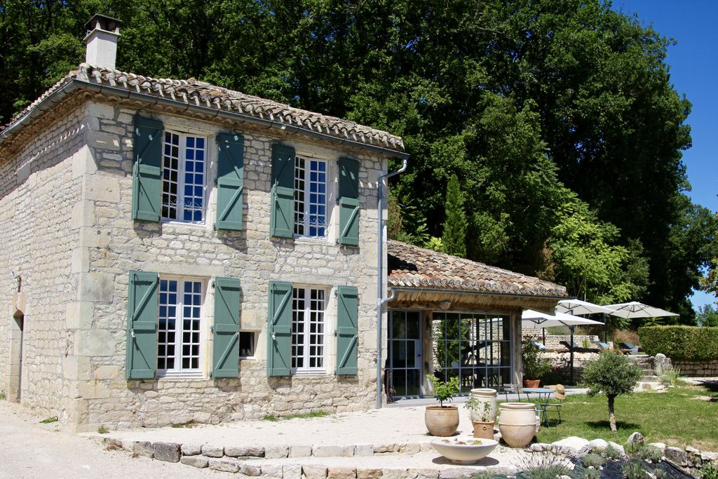 Exterior of Chateau de Latour with white-stoned exterior and washed blue window shutters in Montcuq, France