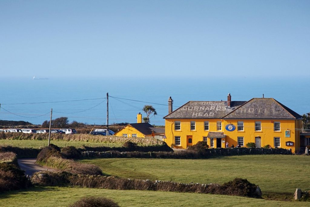 Exterior of The Gurnard's Head in Cornwall set in the countryside with view of sea just behind