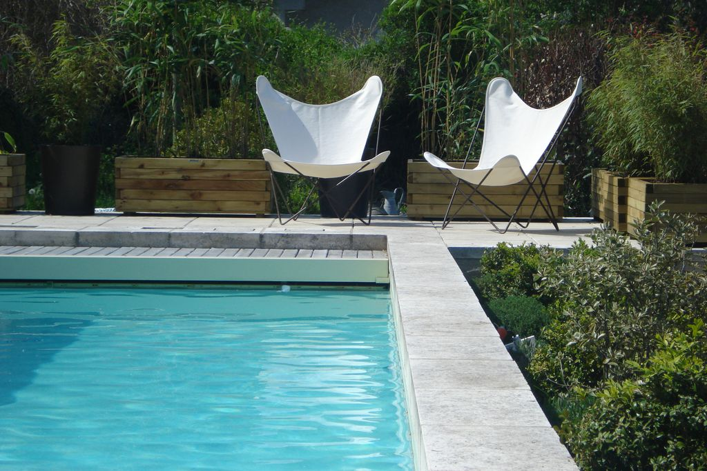 Pool area and seating outside at Les Jardins de Brantome in Dordogne, France