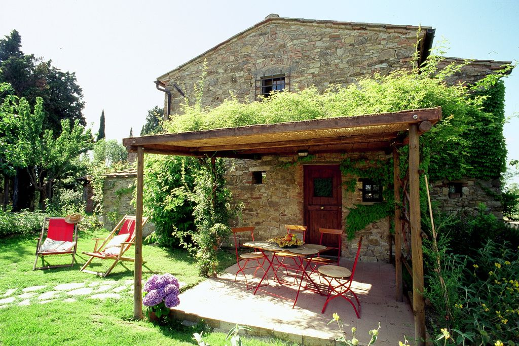 Outside terrace and grounds at Fattoria Casa Sola in Florence, Italy with sheltered area and deck chairs in a sunny spot