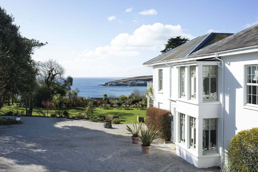 Exterior view of property with expansive lush garden and beautiful view of the sea