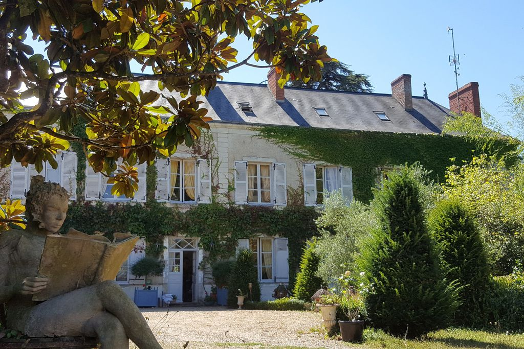 Exterior of Domaine de Bre in Seiches sur le Loi, France with white wooden shutters and a wild garden