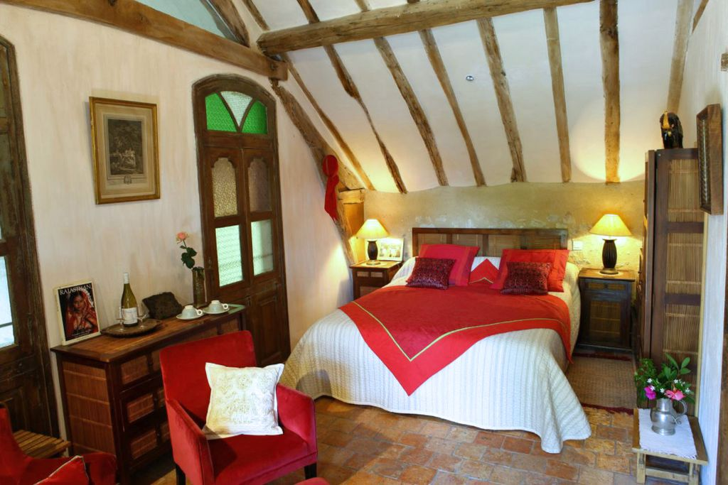 The bedroom at Domaine de Bre in France with lots of original wooden features and pops of red furnishings, with a bottle of wine and fresh flowers on the side
