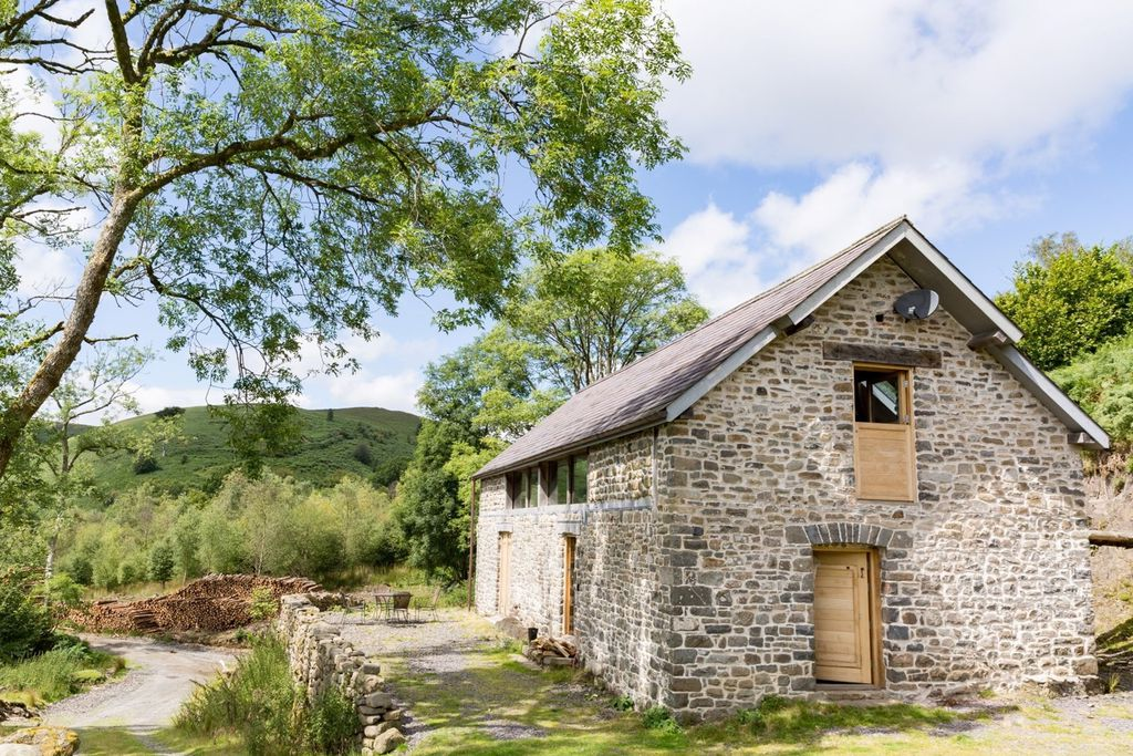 Exterior of Red Kite Barn in Powys, Wales, built from stone and with a lovely rustic seating area and lush surroundings
