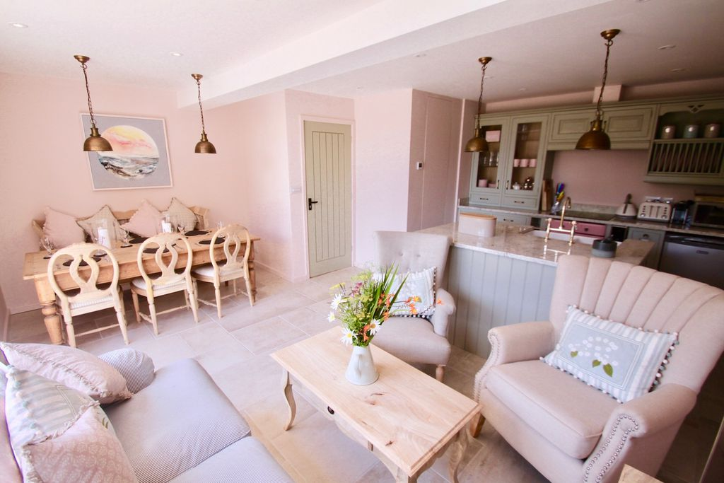 Open plan kitchen and dining area at The Stables in Salcome, Devon with pastel-hued walls and furniture. Table laid for six and fresh flowers on the table, with French doors opened out onto the terrace