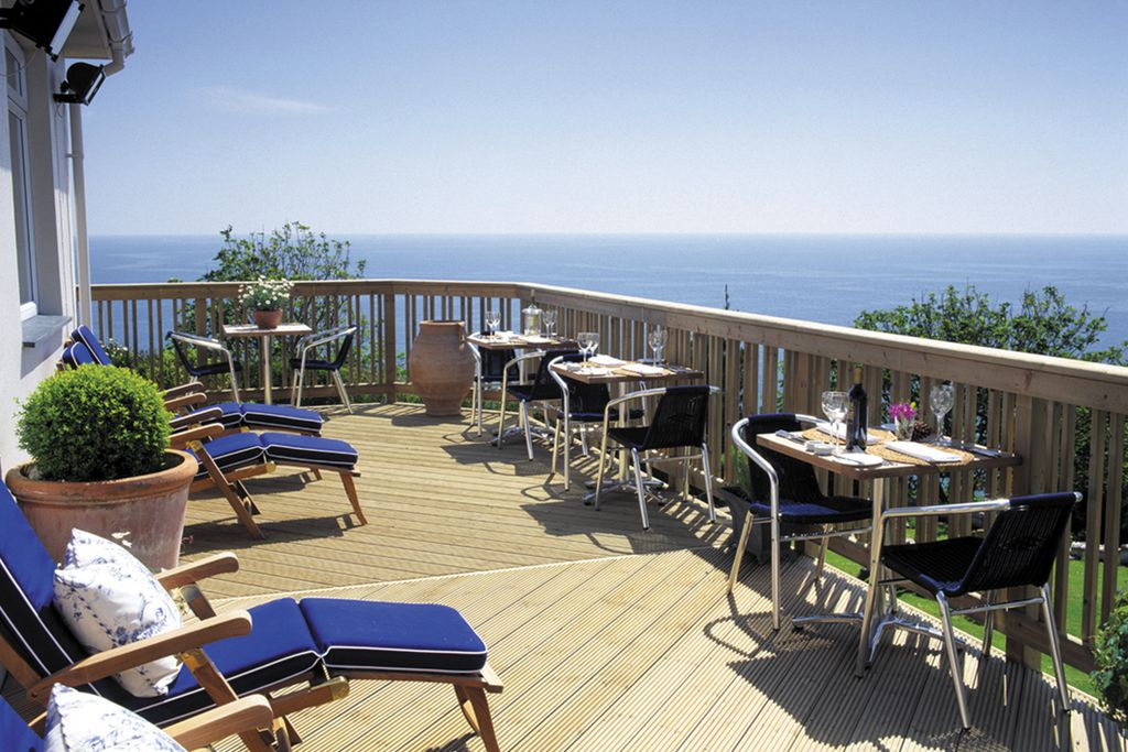 Outdoor terrace for al fresco dining, as well as sunbathing, at the Driftwood Hotel in Portscatho in Cornwall with panoramic views of the sea