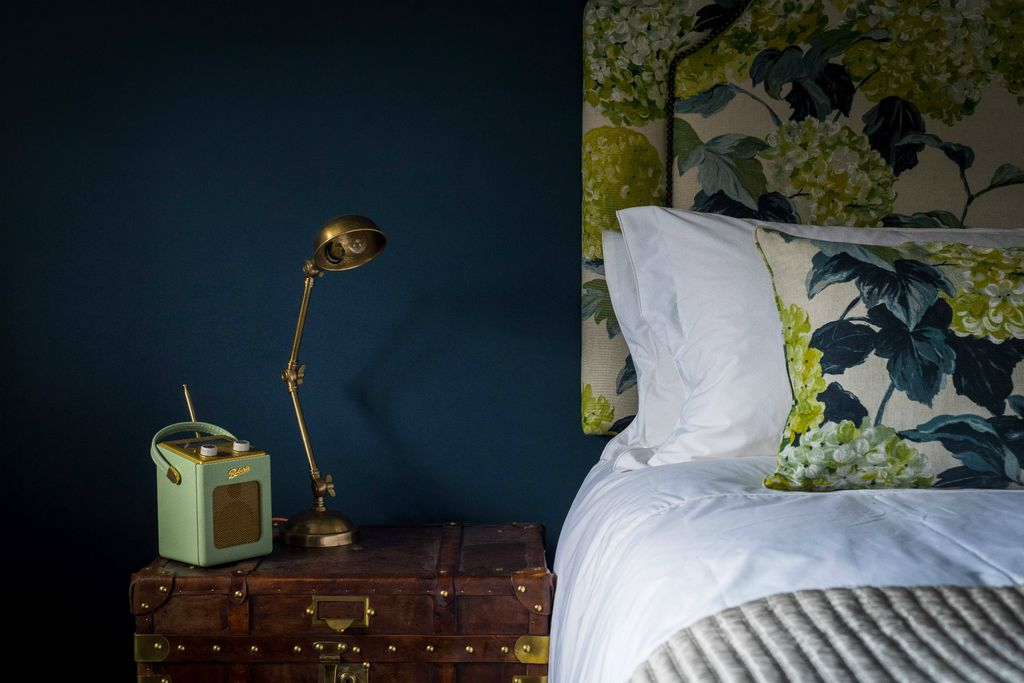 Bedroom at Hooppells Tor with fresh white linen against a luxurious dark blue wall and a Roberts radio, gold desk lamp and wooden chest as bedside table