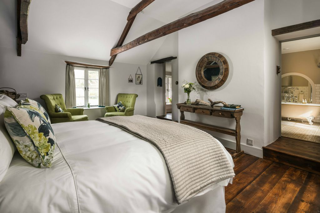 Light and airy bedroom at Hooppells Tor with two armchairs by the window, a lovely wooden table and walkway through to a roll top bath
