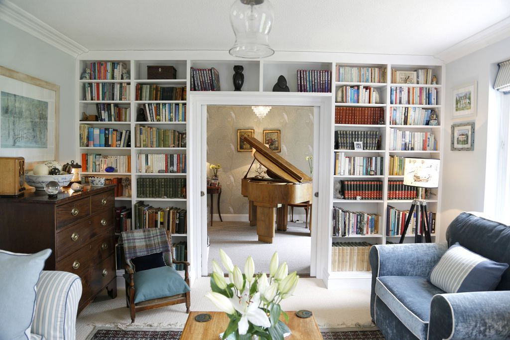 Living room at Greenhill House in Lyme Regis, Dorset with entire wall of one side of room filled with books, and an arch through to piano room with gorgeous old, wooden piano