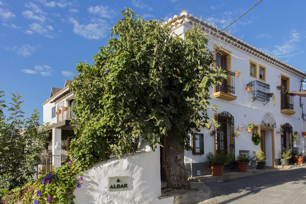 Exterior of the gorgeous Casona Granado in Almeria, Spain with white-washed walls and iron balconies, and lots of plants surrounding the entrance