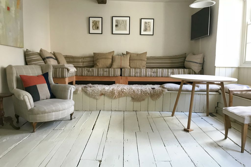Lounge area at Atelier Hay in Hay on Wye with rustic uneven wooden flooring and large raised seating area, all in neutral tones
