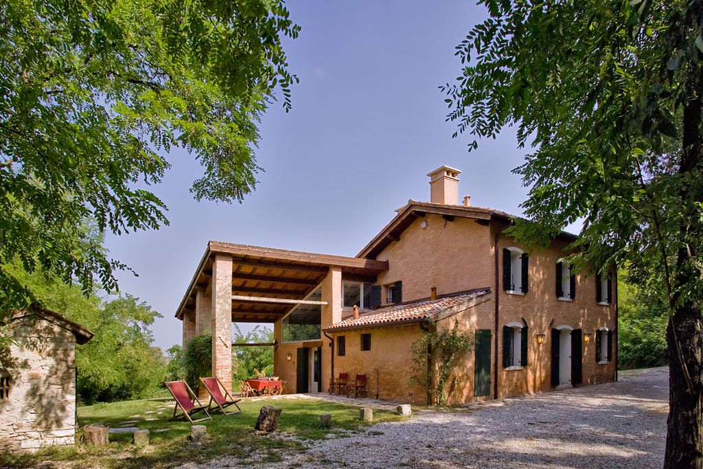 View of the gorgeous, traditional Villa Lieta in Padua, Italy, from the rustic grounds with deckchairs for lounging in and a large table for al fresco dining