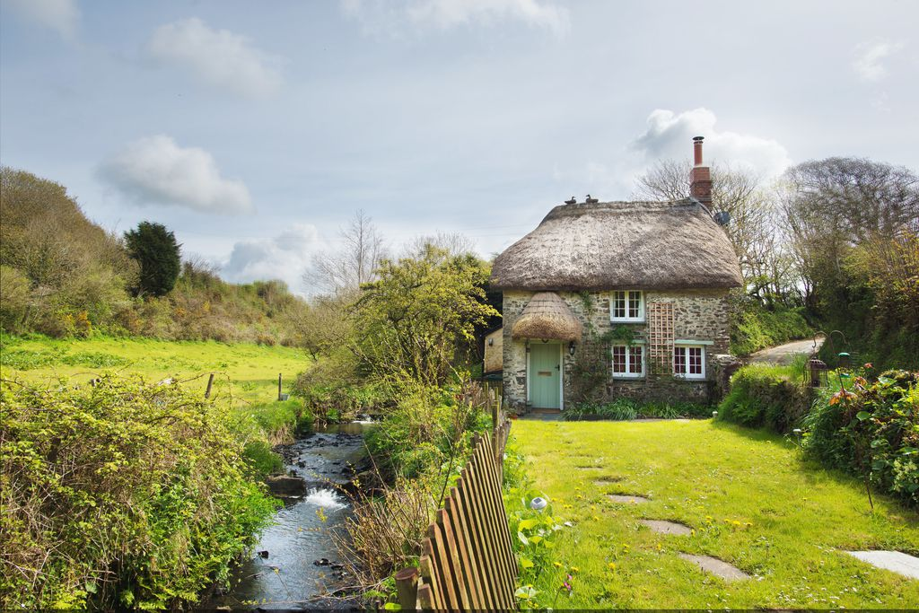 View of thatched-roofed Philham Water Cottage in Bideford, Devon from front garden - a secluded spot with a babbling brook alongside the cottage