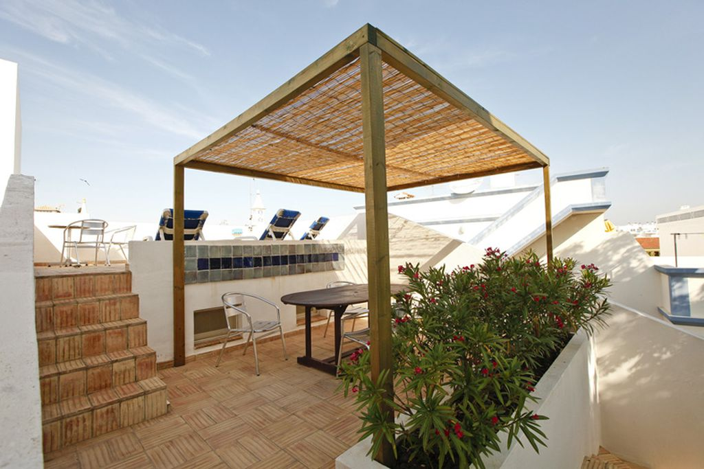Sunny rooftop terrace at Casa Roberto in Santa Luzia, Algarve, Spain with sun loungers and sheltered seating area for dining