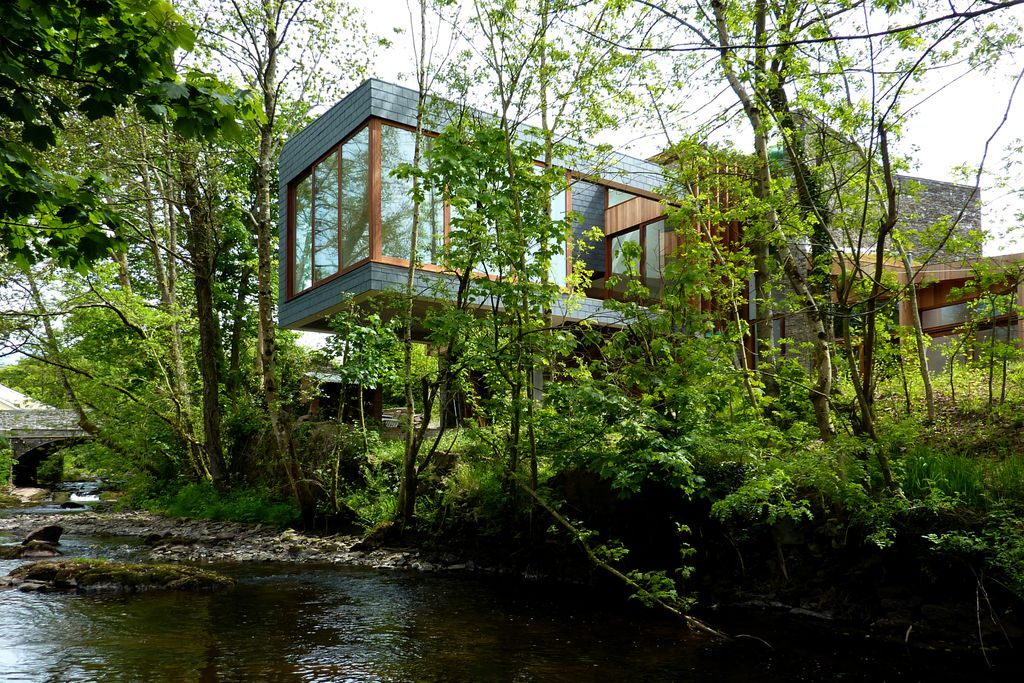 View of Ty Hedfan in Brecon, Powys, Wales through the trees - a stylish building with glass windows, right next to the river