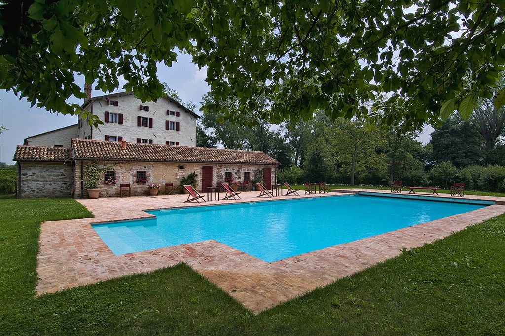 Exterior of lovely Italian farmhouse Villa Bencontenta in Padua, Italy with large swimming pool and a few deckchairs to lounge in