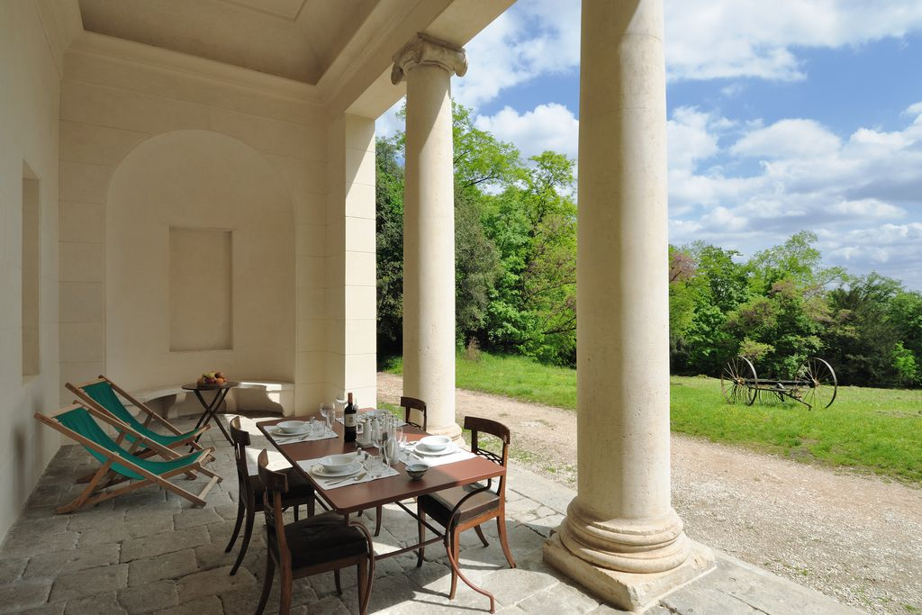 View from outdoor terrace at Villa Tempietto in Padua, Italy with deckchairs and a table laid for four
