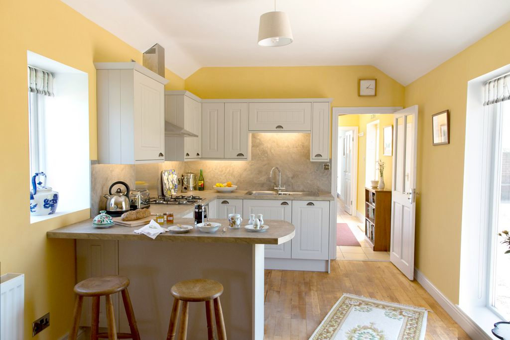 Lovely, modern kitchen area at Old Estate Office Cottage painted in a light yellow, and with a breakfast bar for sitting at