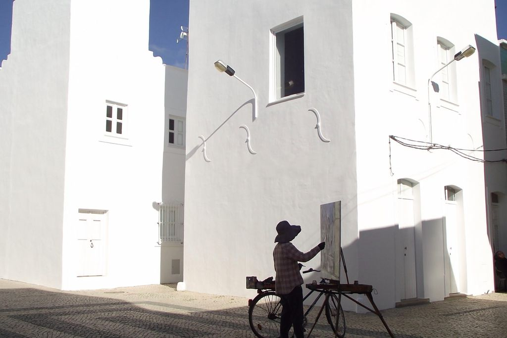 Exterior of Casa Gaibeu in Olhao, Algarve, Portugal with local man painting the town's white-washed buildings next to his bike