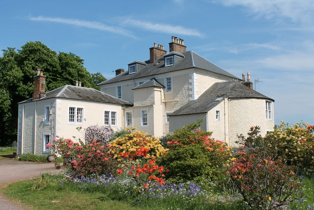 Exterior of pretty Knockhill House in Dumfries and Galloway in Scotland with large garden full of blooming colourful flowers