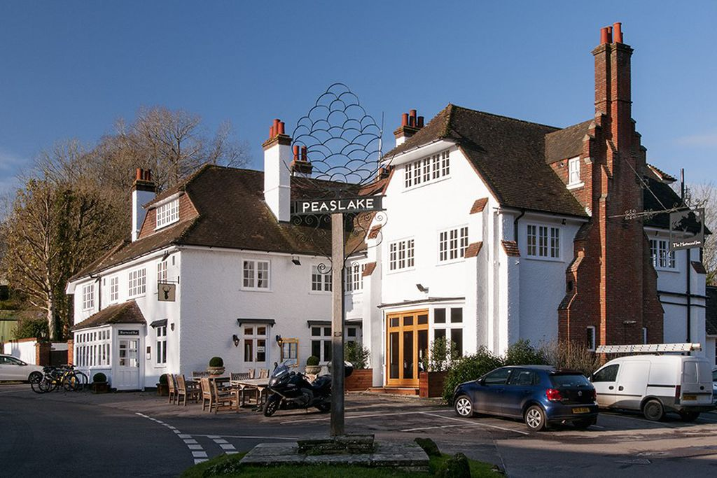 View of Hurtwood Hotel in Peaslake, Surrey, England with outdoor seating area and space for parking