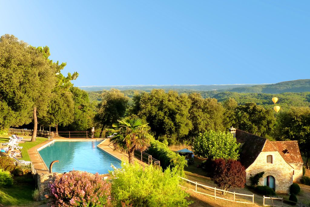 Pool area in lush green grounds with sunloungers and view across the valley at Gites du Perigord in Dordogne, France