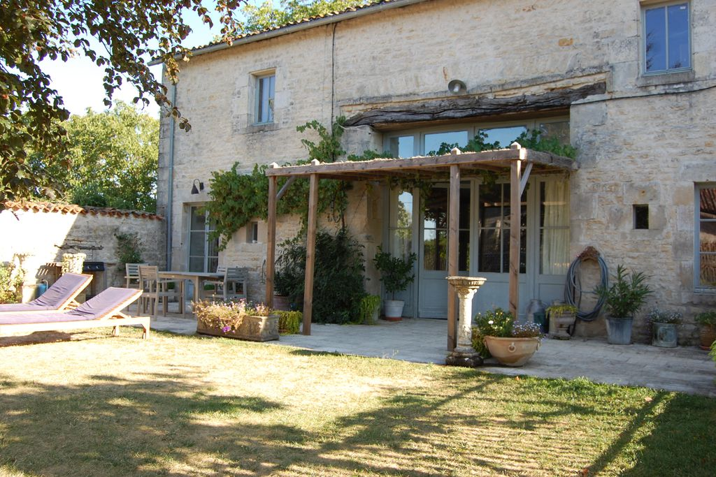 Exterior of La Laitere in Deuz Sevres, France lovely outdoor terrace for al fresco eating and sun loungers in the garden