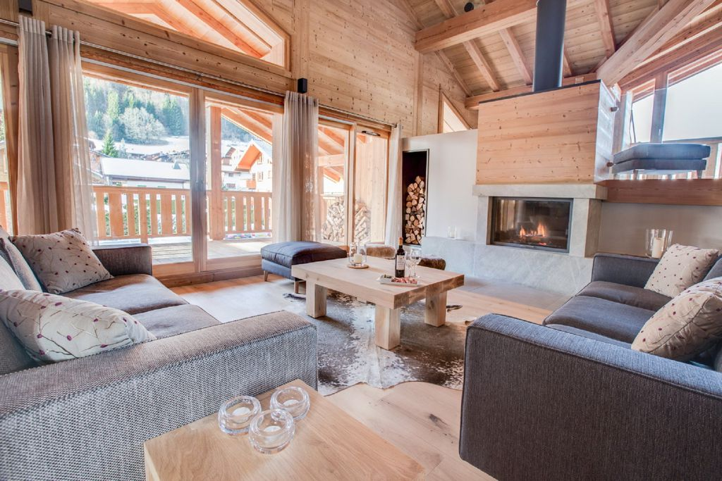 Contemporary living room with cosy woodburner inside Les Roches Noires in Morzine, Savoie