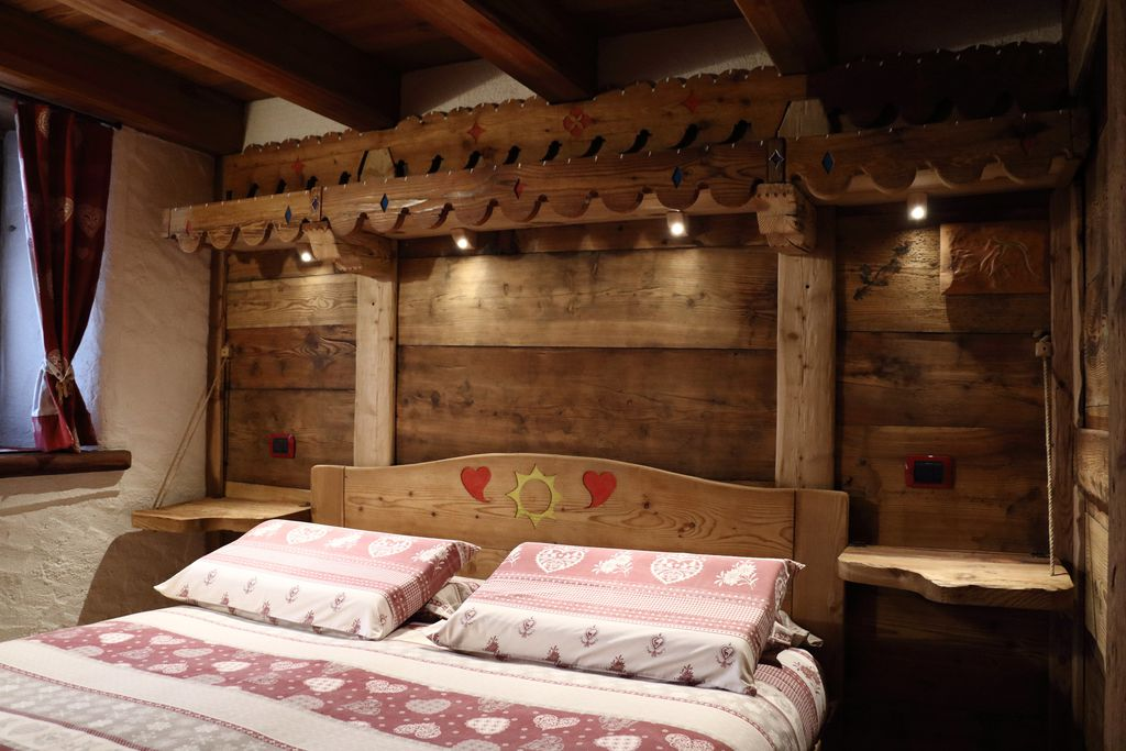 Wooden, hand-crafted bed inside of La Maison de grand Maman in Aosta Valley, Italy